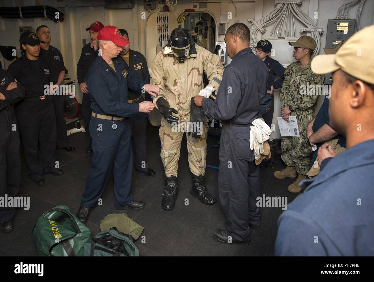 SAN DIEGO (June 26, 2018) Senior Chief Culinary Specialist Anthony Hooper, left, and Ship's Serviceman Seaman Jaylan Eady, right, from Whiteville, N.C., help Logistics Specialist 2nd Class Donald Eugene, from Miami, don a chemical, biological and radiological (CBR) overgarment during a CBR training exercise aboard the amphibious assault ship USS Bonhomme Richard (LHD 6). Bonhomme Richard is currently in its homeport of San Diego, preparing for an upcoming scheduled deployment. - Stock Image