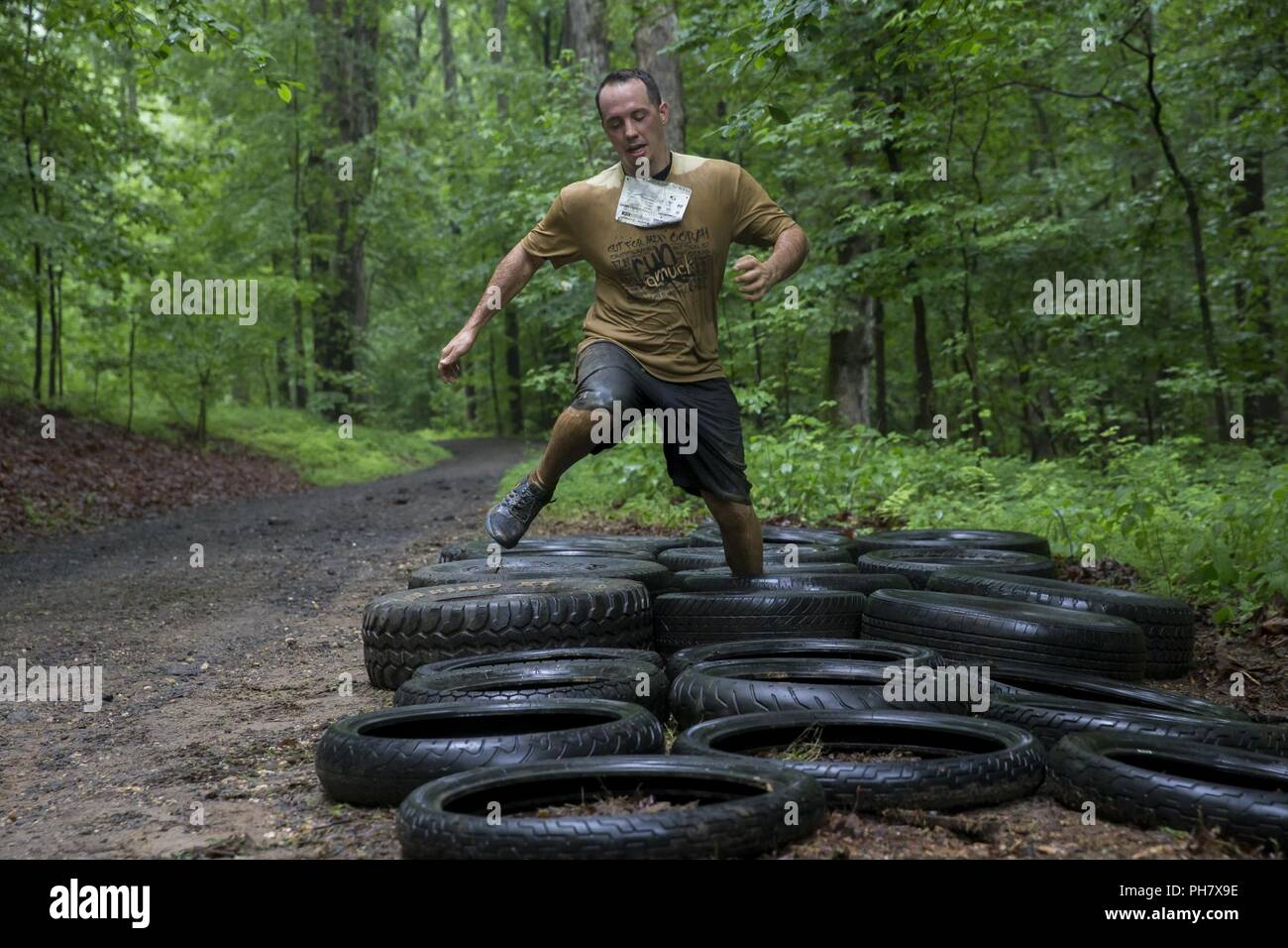 A Participant navigates a tire obstacle during the annual Marine Corps Marathon (MCM) Run Amuck at Marine Corps Base Quantico, Va., June 23, 2018. The Run Amuck is the MCM's messiest mud and obstacle course consisting of a four-mile trail with 21 challenges to include body weight exercises, rope climbs, and mud pits. - Stock Image