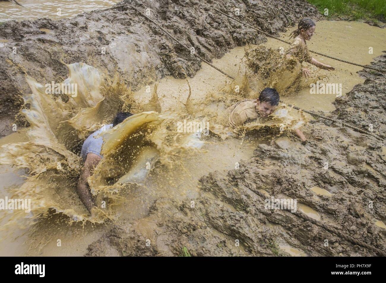 Participants jump into a mud pit during the annual Marine Corps Marathon (MCM) Run Amuck at Marine Corps Base Quantico, Va., June 23, 2018. The Run Amuck is the MCM's messiest mud and obstacle course consisting of a four-mile trail with 21 challenges to include body weight exercises, rope climbs, and mud pits. - Stock Image