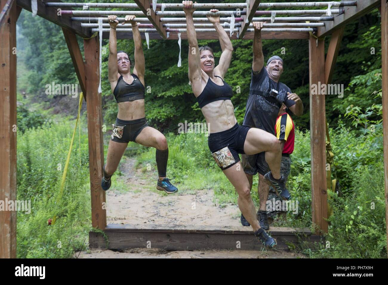 Participants navigate an obstacle during the annual Marine Corps Marathon (MCM) Run Amuck at Marine Corps Base Quantico, Va., June 23, 2018. The Run Amuck is the MCM's messiest mud and obstacle course consisting of a four-mile trail with 21 challenges to include body weight exercises, rope climbs, and mud pits. - Stock Image