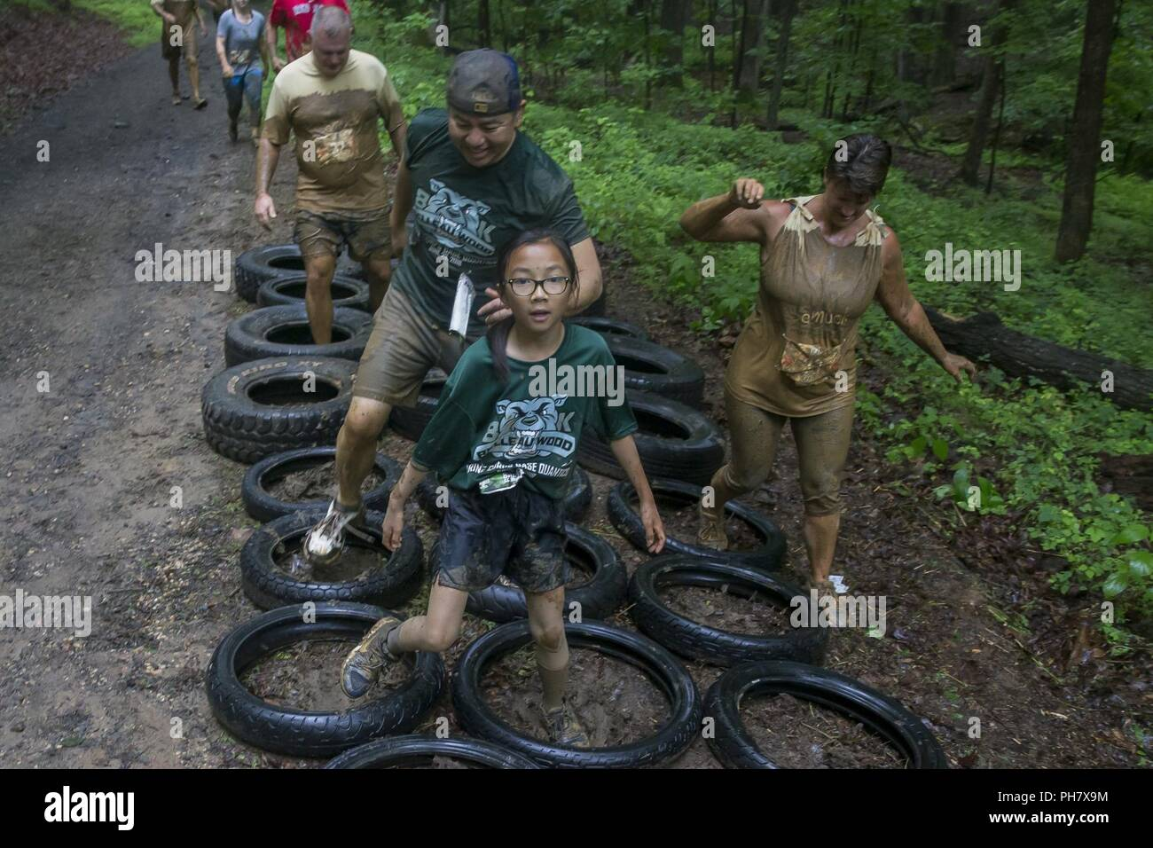 Participants navigate a tire obstacle during the annual Marine Corps Marathon (MCM) Run Amuck at Marine Corps Base Quantico, Va., June 23, 2018. The Run Amuck is the MCM's messiest mud and obstacle course consisting of a four-mile trail with 21 challenges to include body weight exercises, rope climbs, and mud pits. - Stock Image