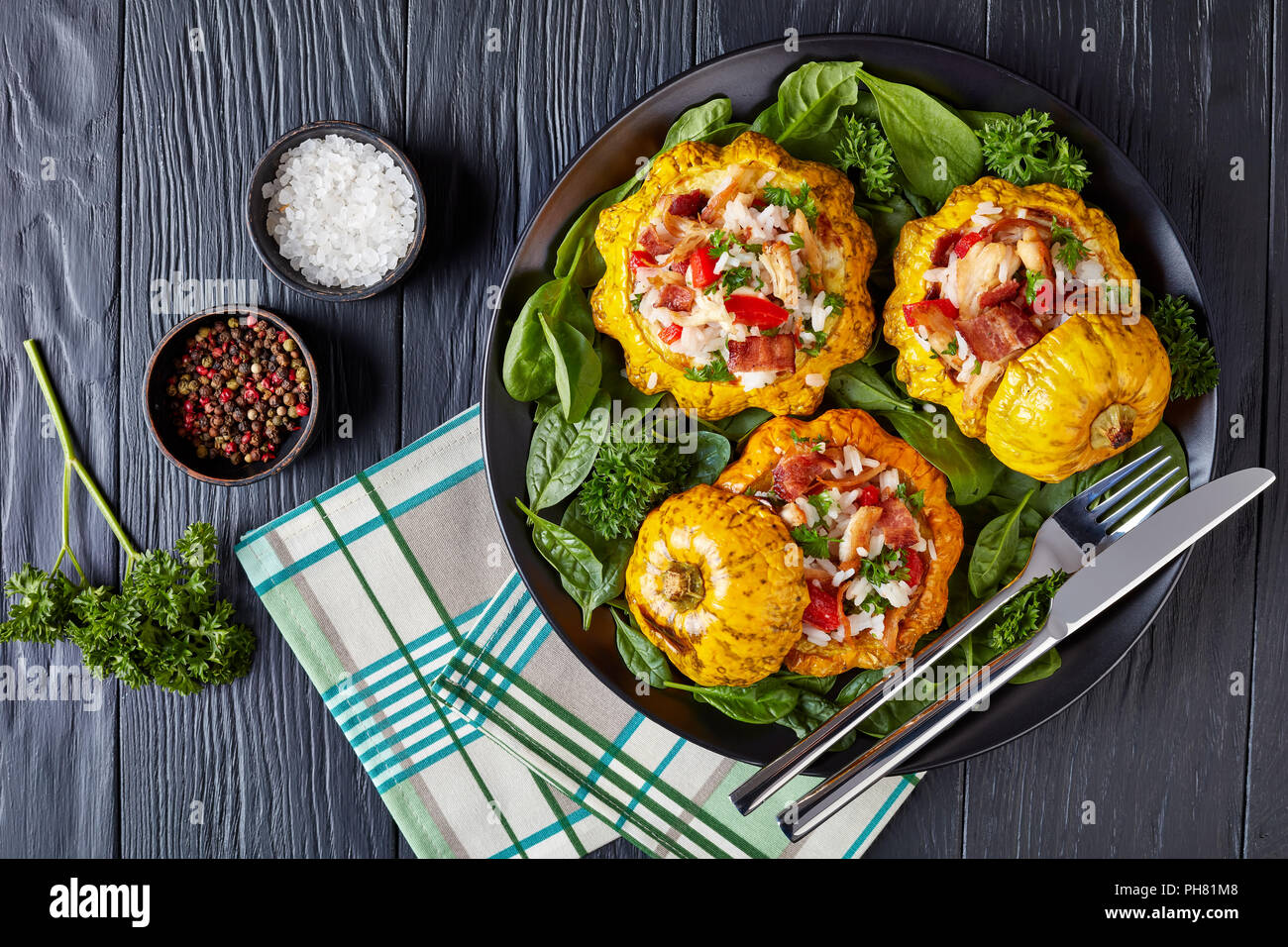 close-up of  baked Pattypan squash stuffed with rice, fried chicken meat, crispy fried bacon, red bell pepper and served with spinach leaves and parsl - Stock Image