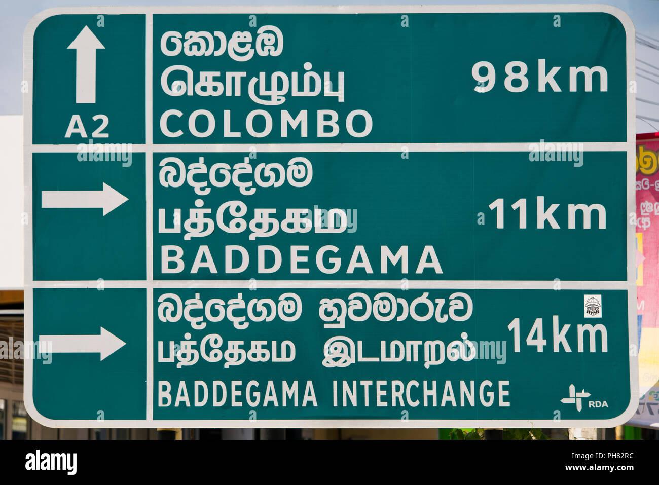 Horizontal close up of a multilingual roadsign in Sri Lanka. - Stock Image