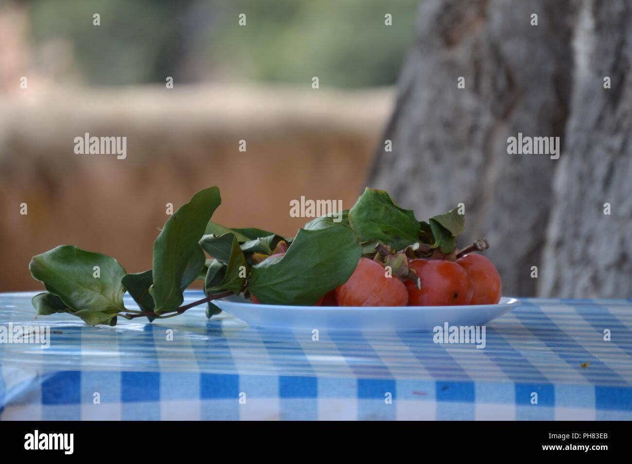 Kaki Früchte auf einem Teller auf einer blau weißen Tischdecke - Stock Image