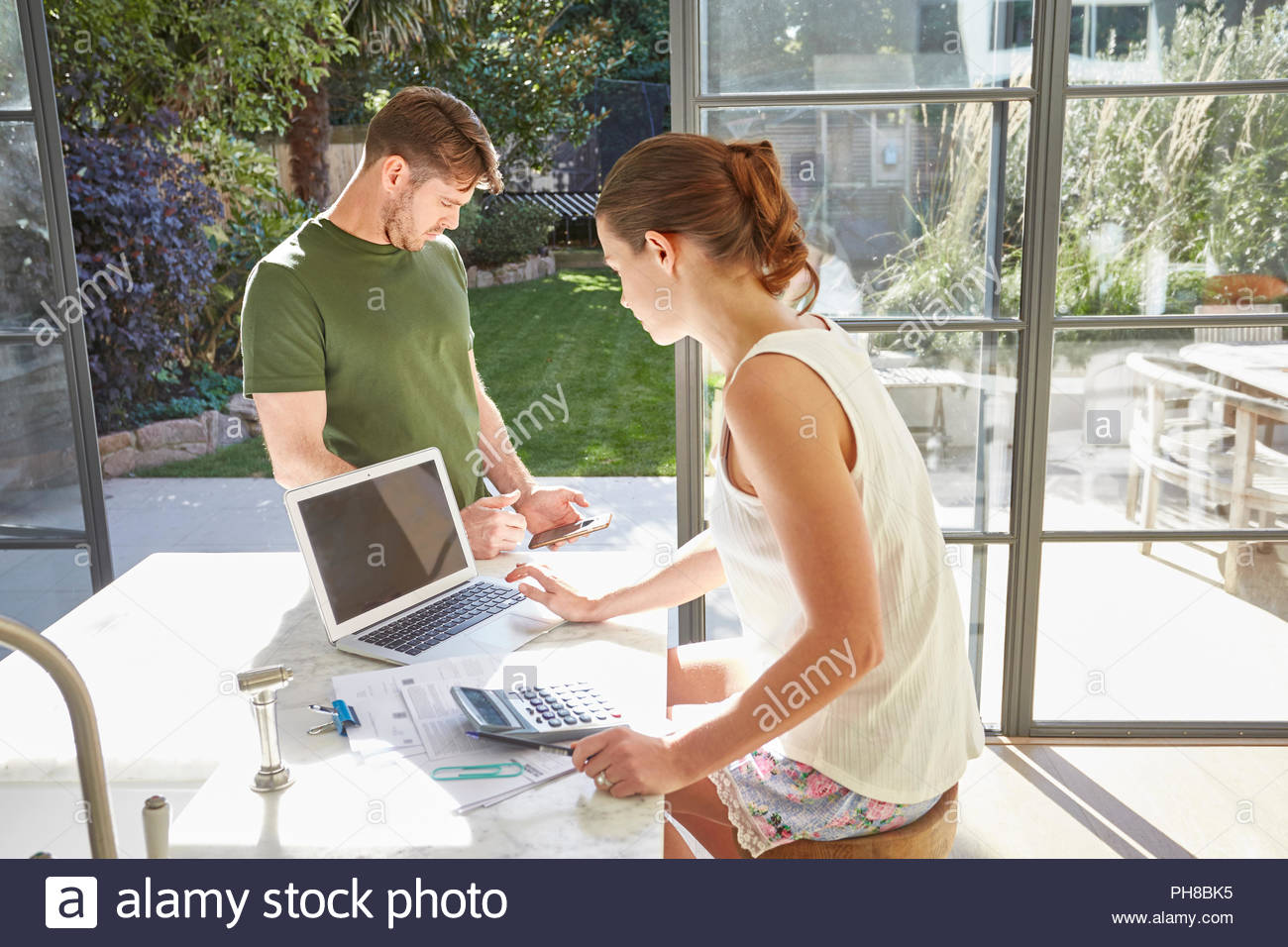 Mid adult married couple working at home. - Stock Image