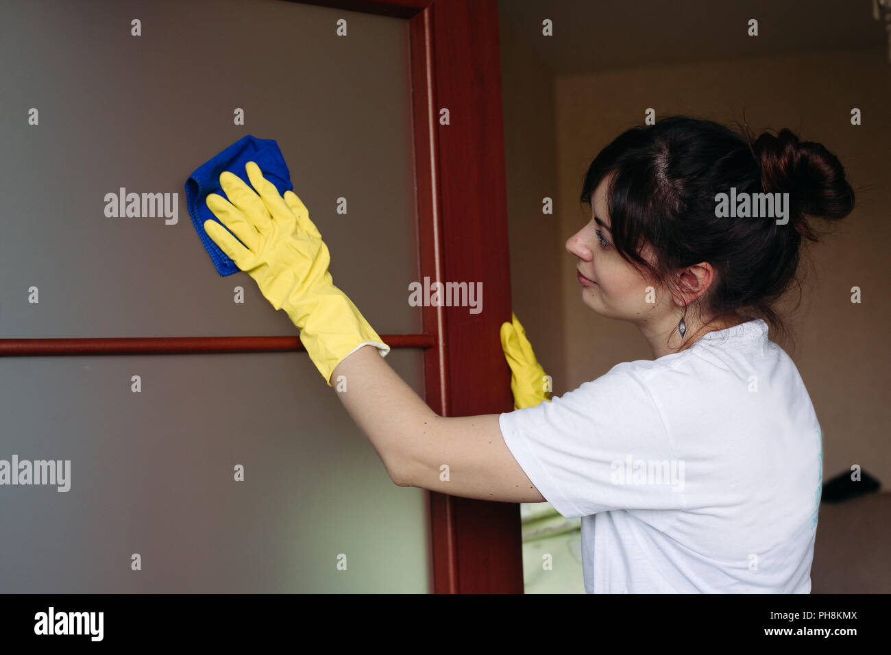 Young brunette housewife cleaning door with rag. - Stock Image