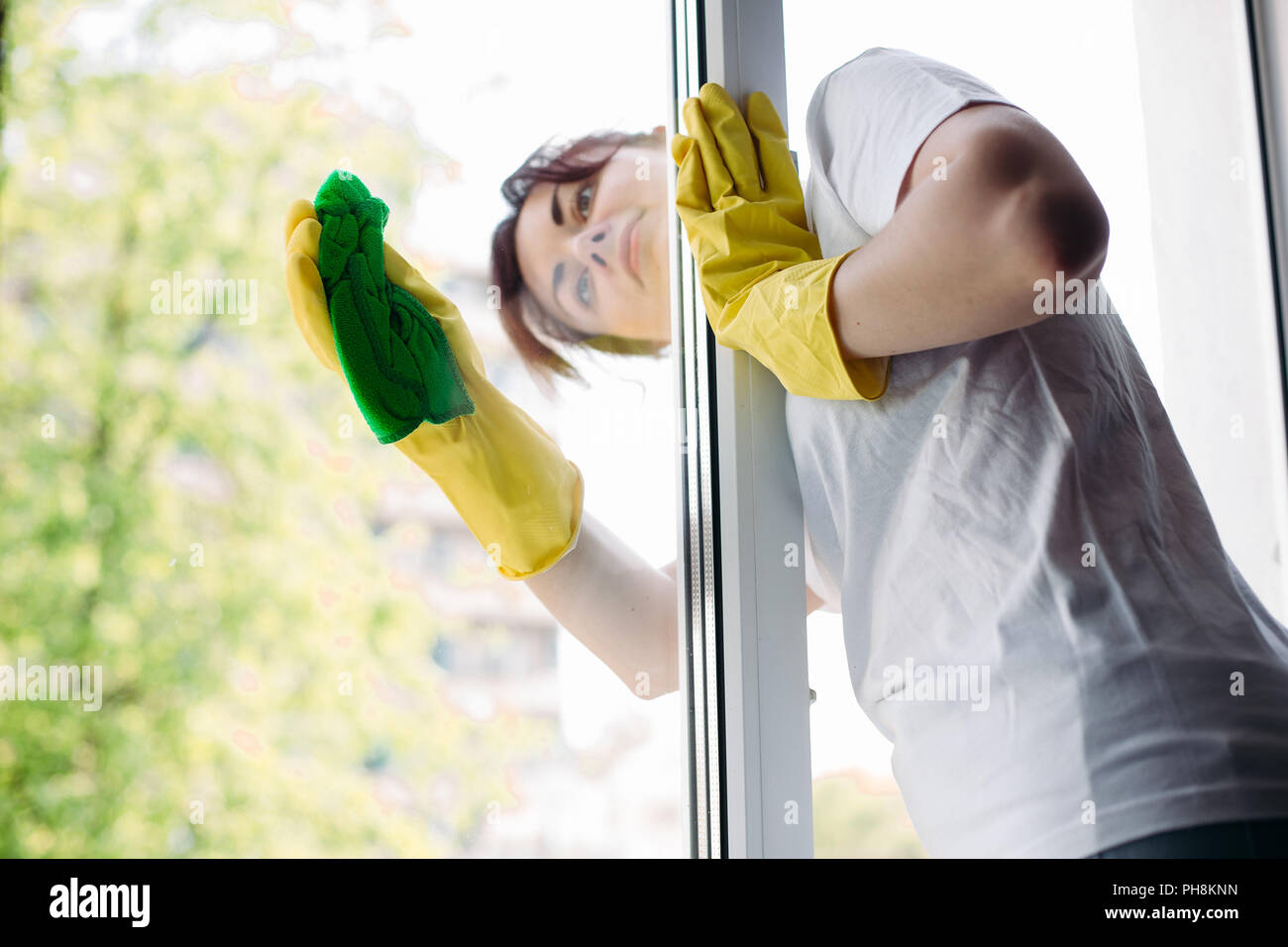 Brunette housewife cleaning big dirty window. Concept of housework and apartment service. - Stock Image