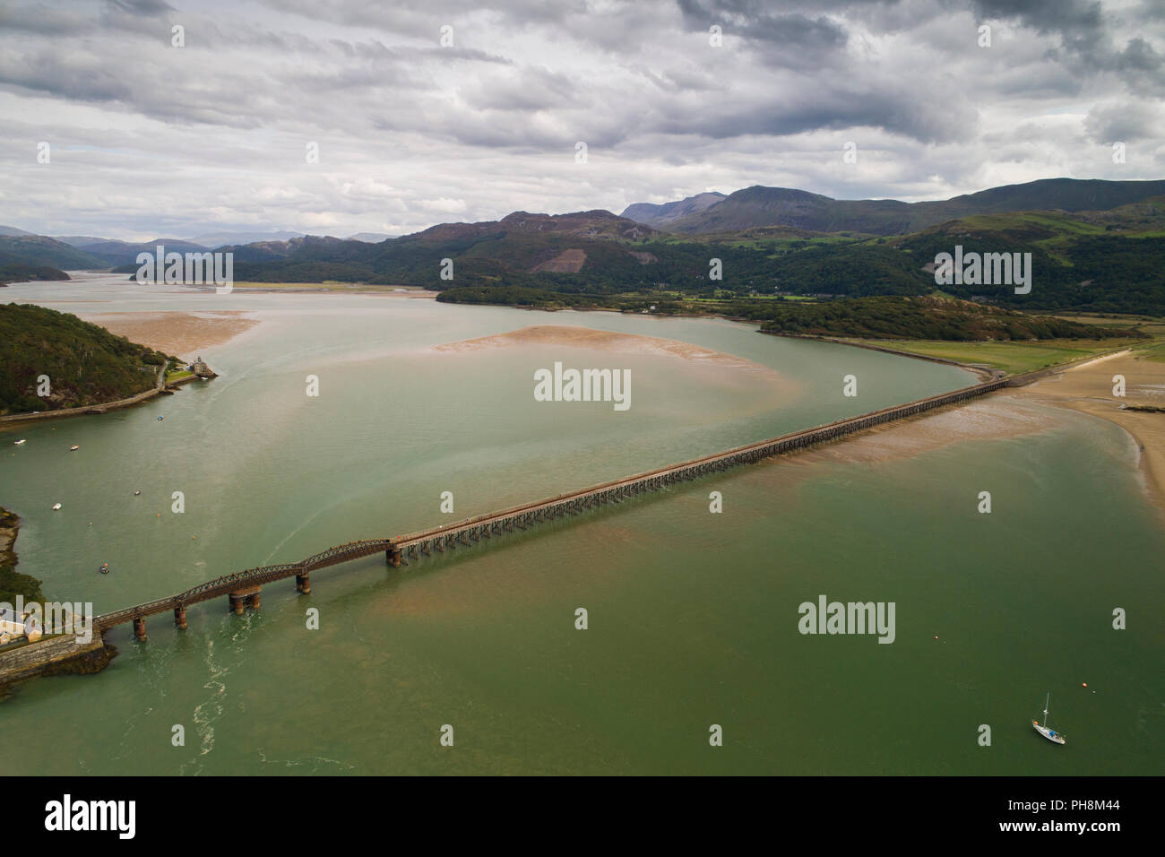 An aerial drone view of the railway viaduct bridge over the Mawddach estuary at Barmouth (Y Bermo / Abermaw in welsh) - a small welsh town and seaside resort , Gwynedd, Snowdonia National Park, North Wales UK (made by a CCA licenced and insured drone operator) Stock Photo