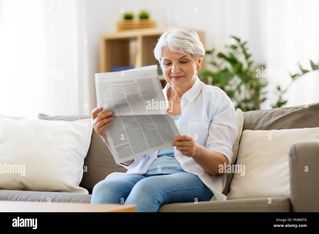 senior woman reading newspaper at home stock photo: 217165542 - alamy