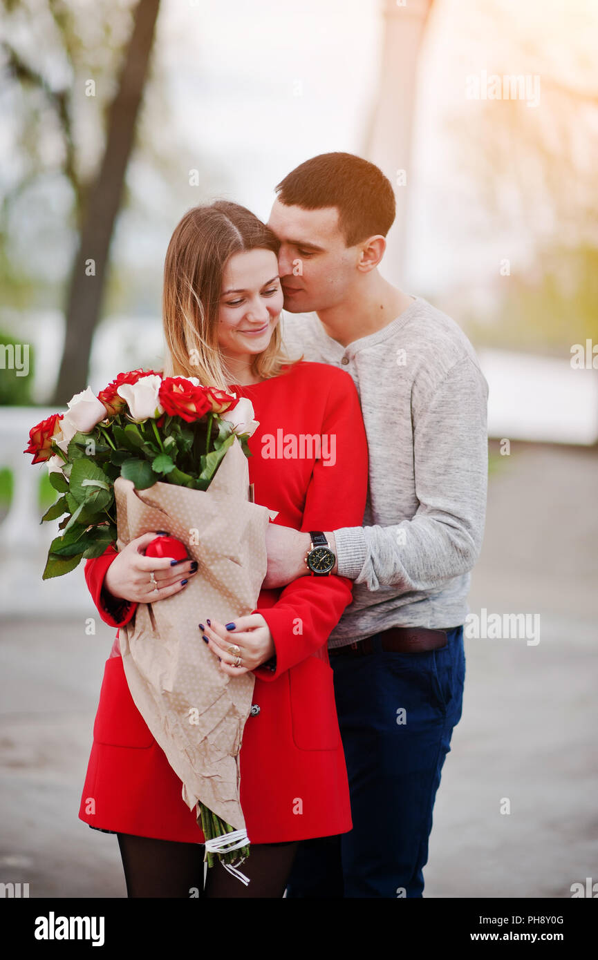 Marriage proposal. Hugging loved couple with bouquet of rose - Stock Image