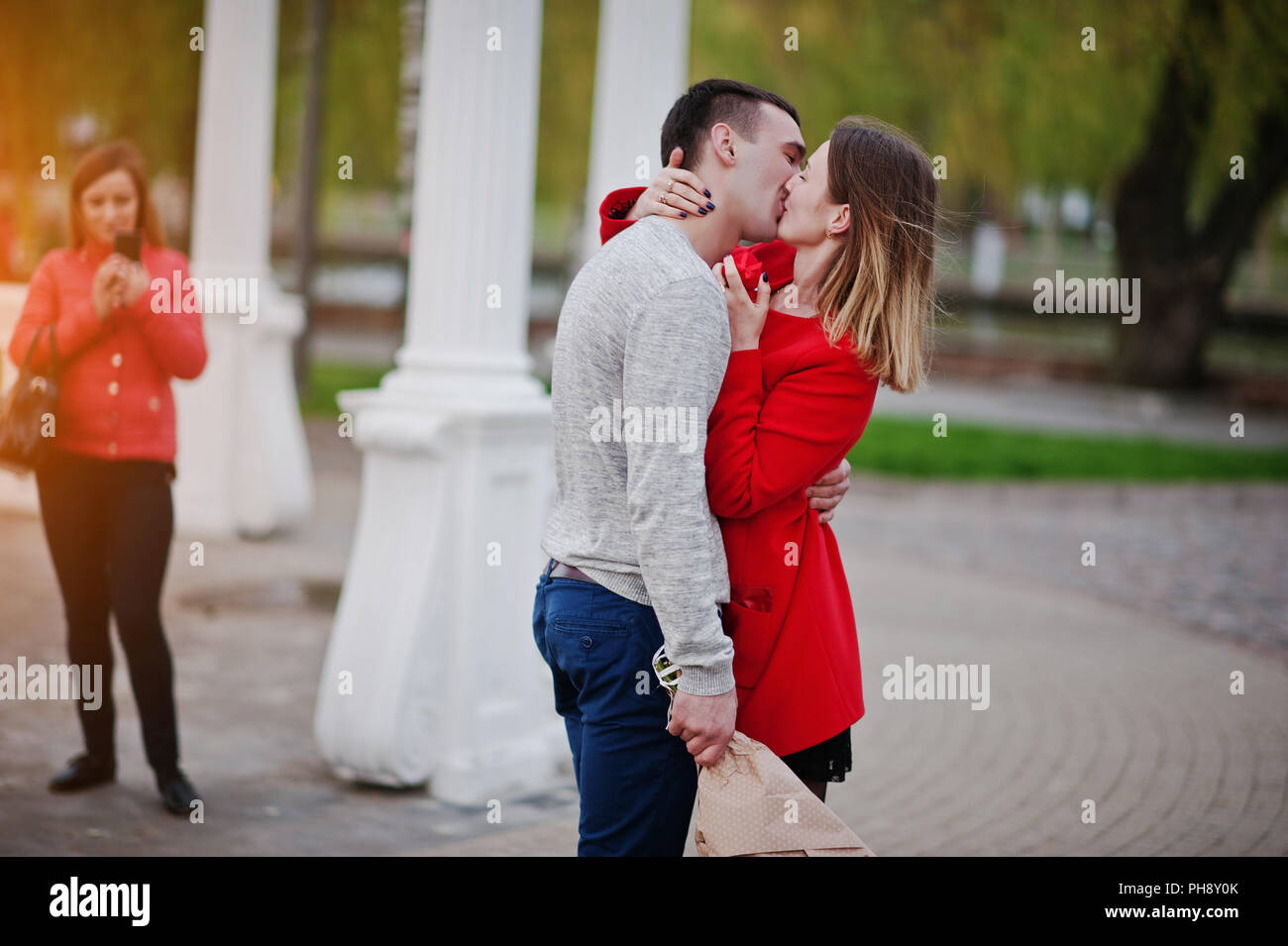 Marriage proposal. Kissed girl and boyfriend with bouquet of flowers - Stock Image