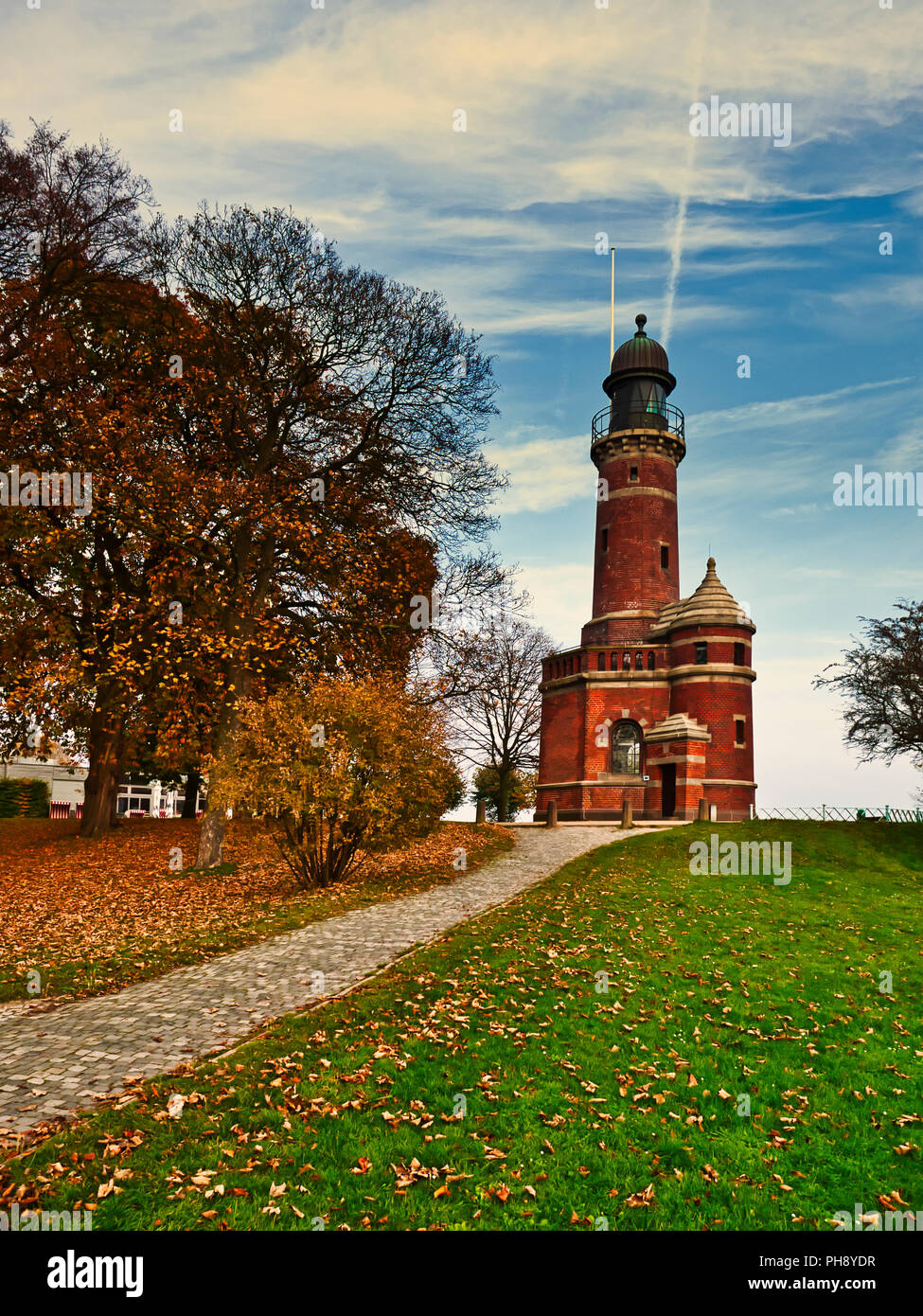 Leuchtturm Kiel-Holtenau. Deutschland. The lighthouse in Kiel harbour. Germany is a popular tourist attraction.  It was originally built in 1784 and its lighthouse tower is 20m tall.  Photographed on a late autumn's day where many of leaves have fallen off the trees covering the grass and path below.  It's a bright day with some light hazy cloud formations. - Stock Image