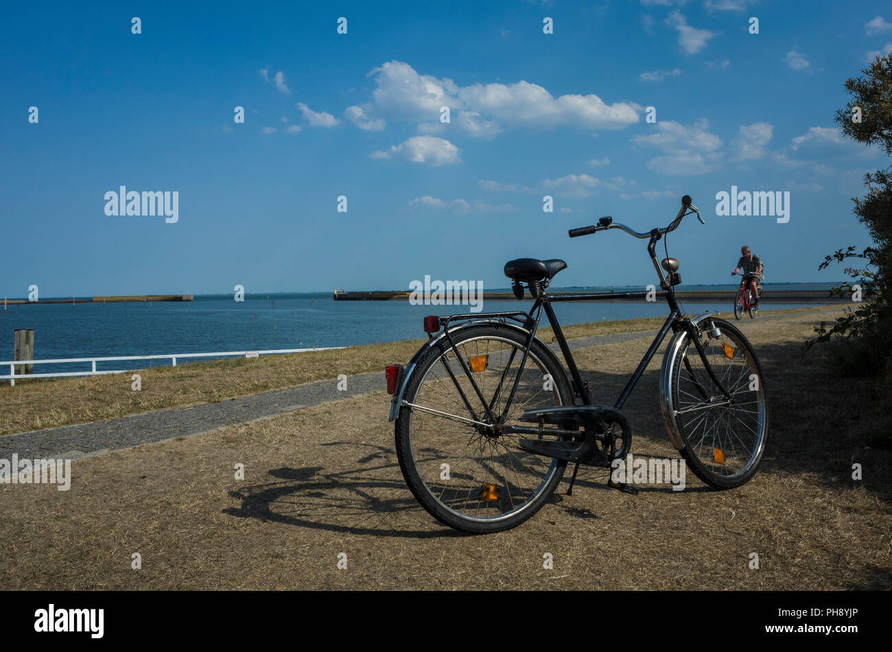Marina Langeoog bei Niedrigwasser. Deutschland.  Traditional German style bicycle parked in front of the harbour.  The old harbour walls that were built in World War 2, WWII, can be seen on the horizon leading out to the sea.  It's a sunny day casting strong shadows from the bicycle and hedgerow with only a few white puffy clouds in the clear sky.  A tourist is cycling into the scene along the narrow harbour road.  The grass verges have dried out and lost their colour in the 2018 heat wave.  The deep blue sea contrasts the warm blue sky. - Stock Image