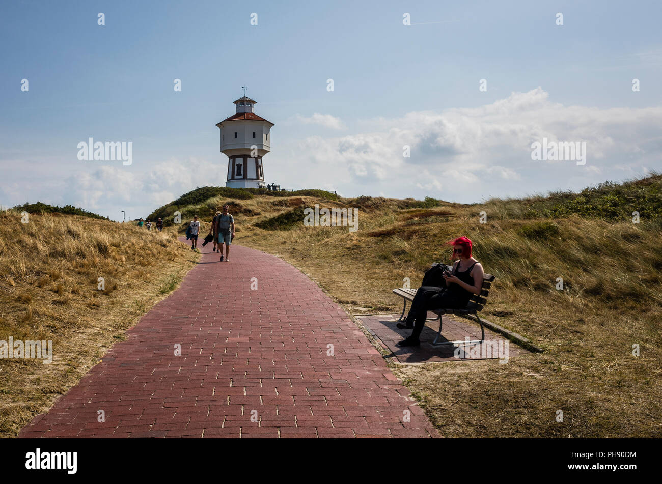 Water Tower, Langeoog. Germany, Deutschland.  A pathway leads towards a tourist attraction, the iconic white water tower - Wasserturm.  A young woman, with red hair, sits on a public  bench to check her mobile phone.  The grass on the sand dunes have been bleached by the sun during the summer's heat wave. - Stock Image