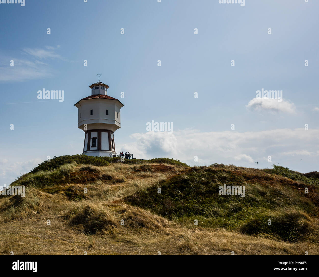 Water Tower, Langeoog. Germany, Deutschland.  A pathway leads towards a tourist attraction, the iconic white water tower - Wasserturm. The grass on the sand dunes have been bleached by the sun during the summer's heat wave.  The photograph is back-lit creating a light blue sky and deep shadows cast towards the viewer - Stock Image