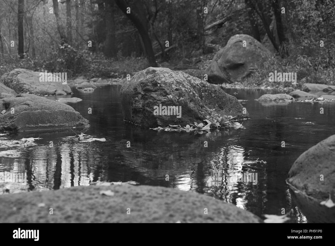 black and white picture of a rocky creek stream. - Stock Image