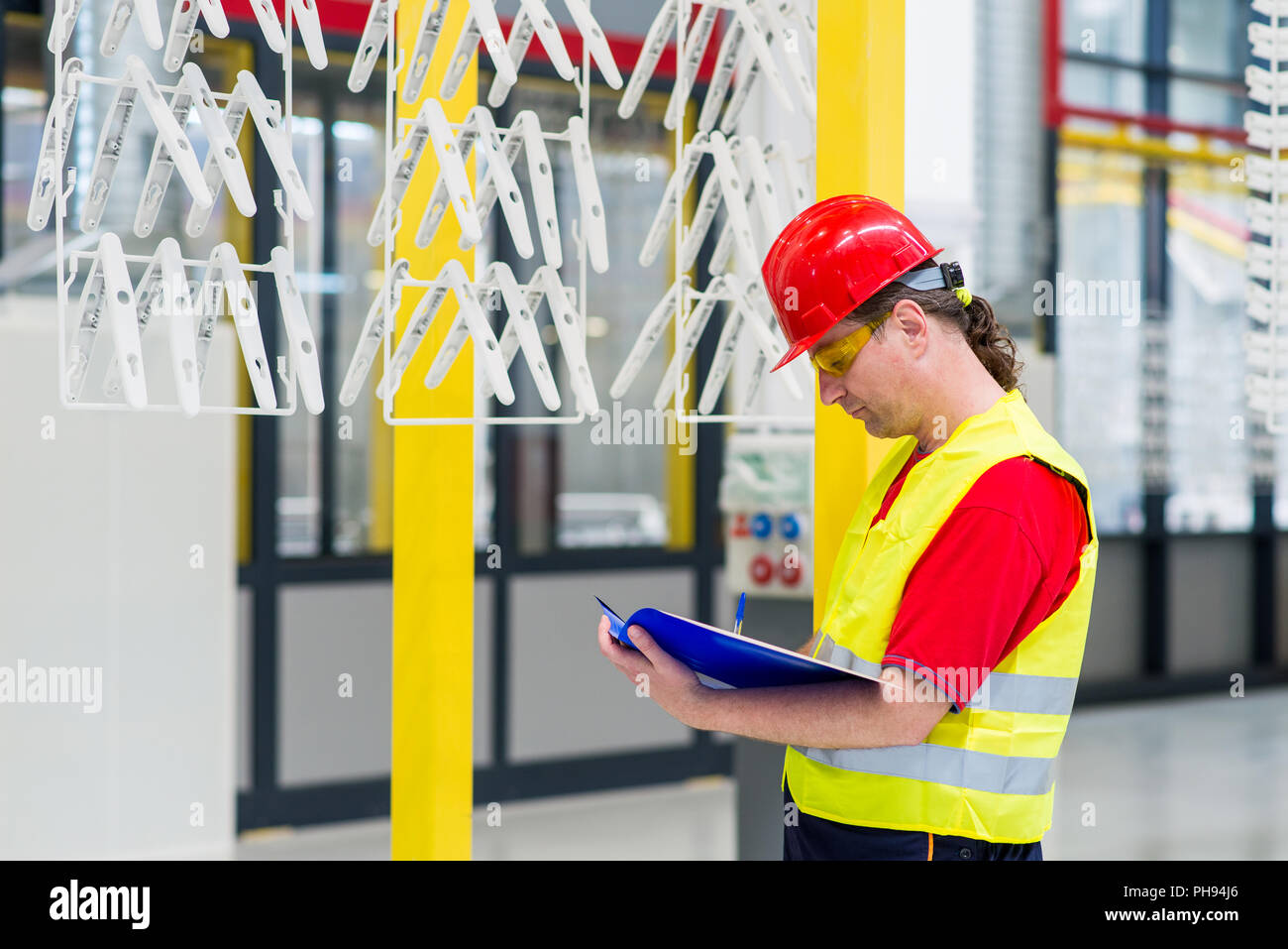 Factory supervisor checking production line for quality control - Stock Image