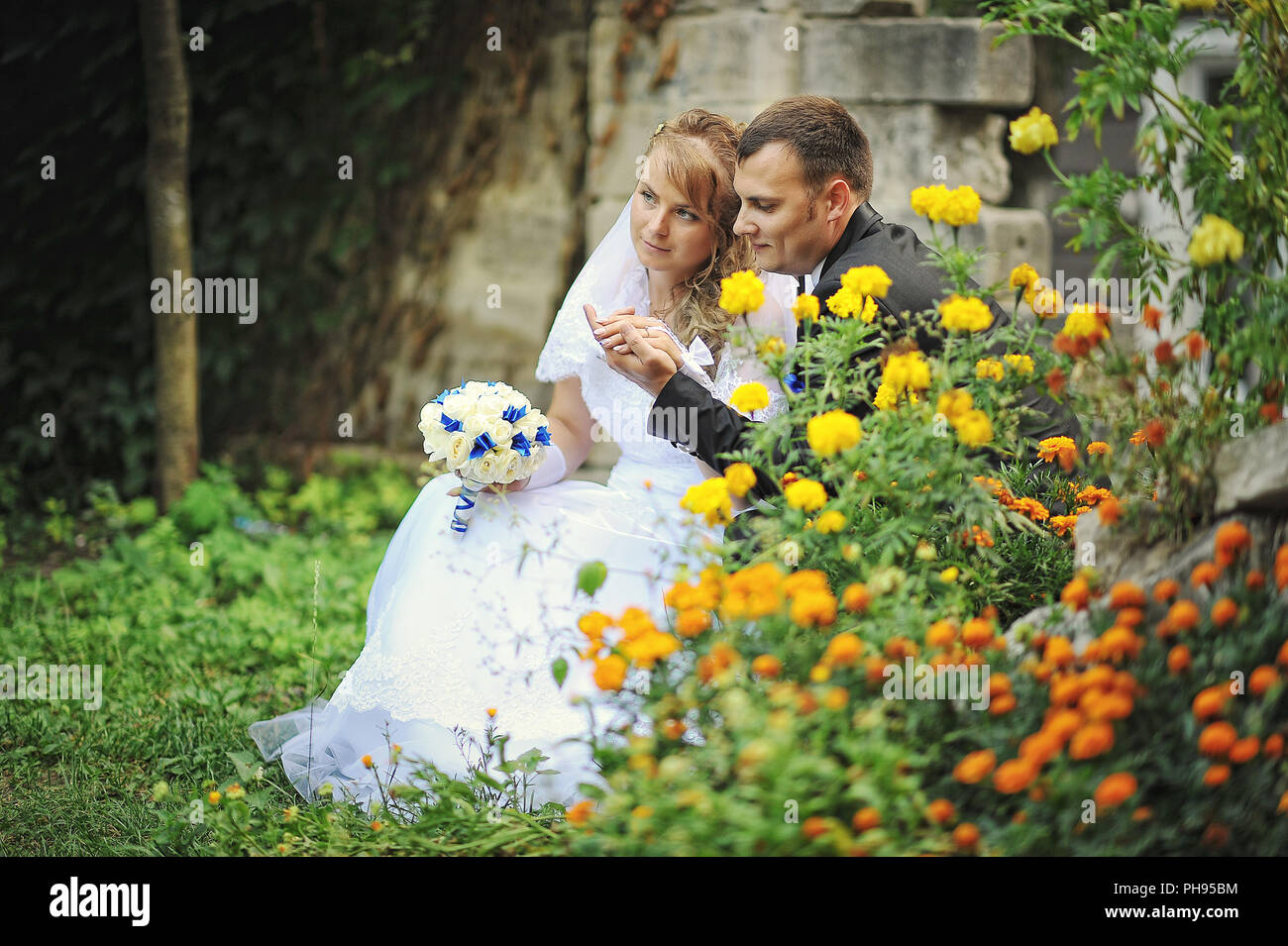 Newlyweds siting near flowers and holding hands - Stock Image