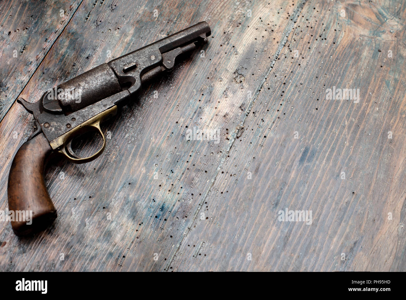 Vintage pistol on old wooden background with space for text