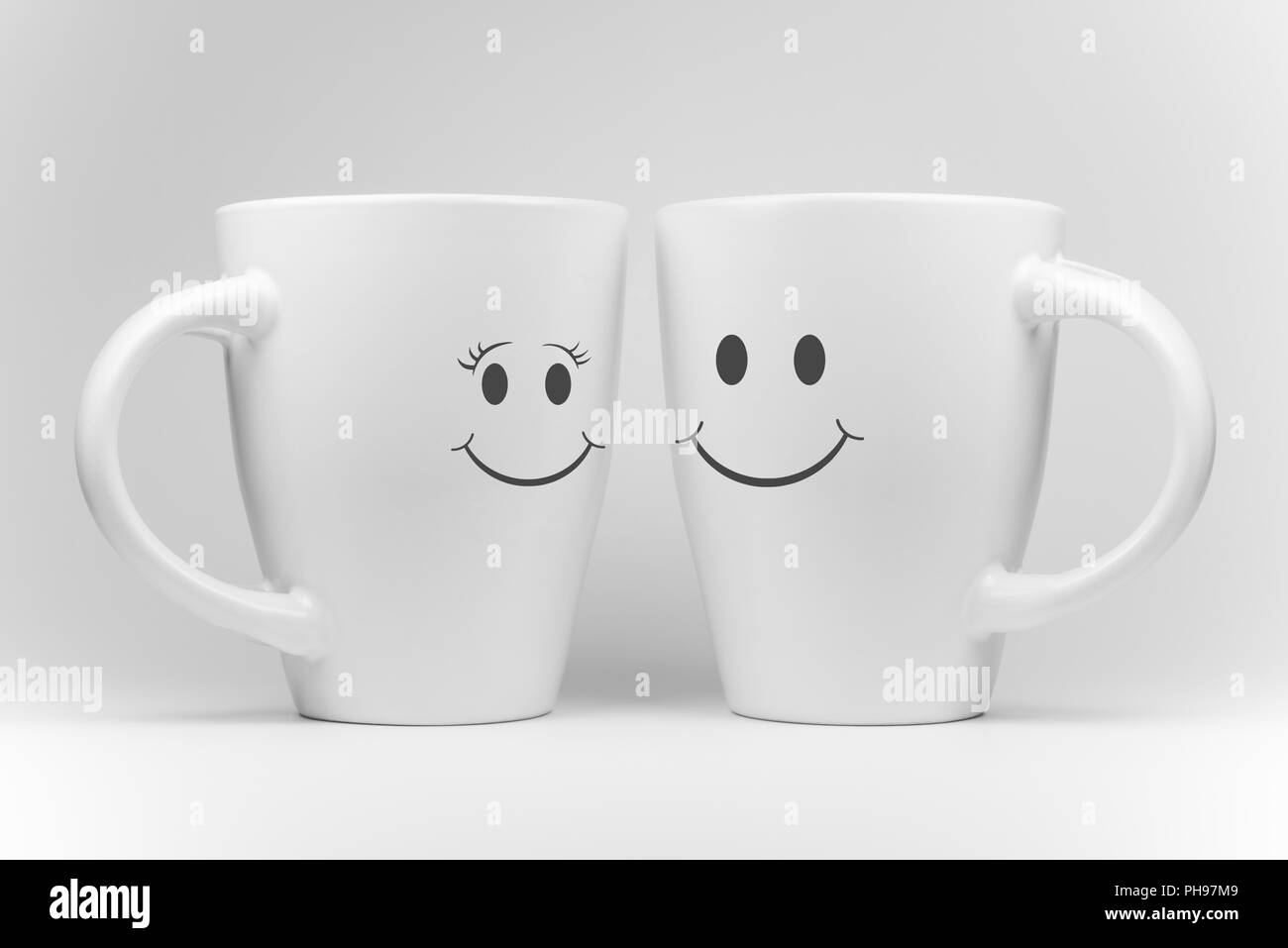 Two white mugs with facial expressions - Stock Image