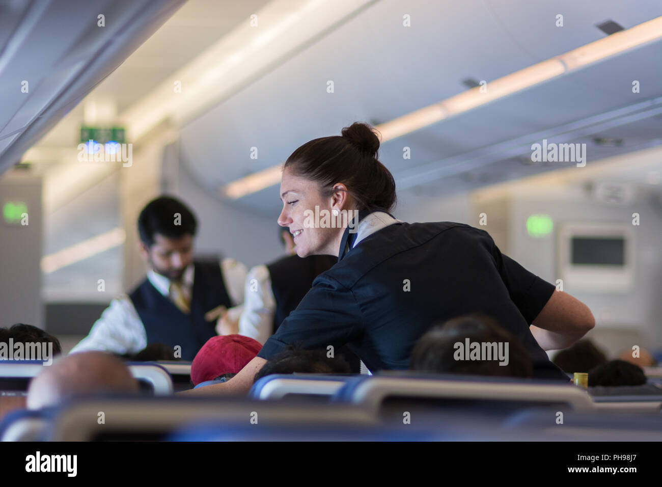 Mumbai, India - July 8, 2018 - Flight attendants speaking with a passenger sitting in the economy class of the route Munich - Mumbai of Lufthansa Airl - Stock Image