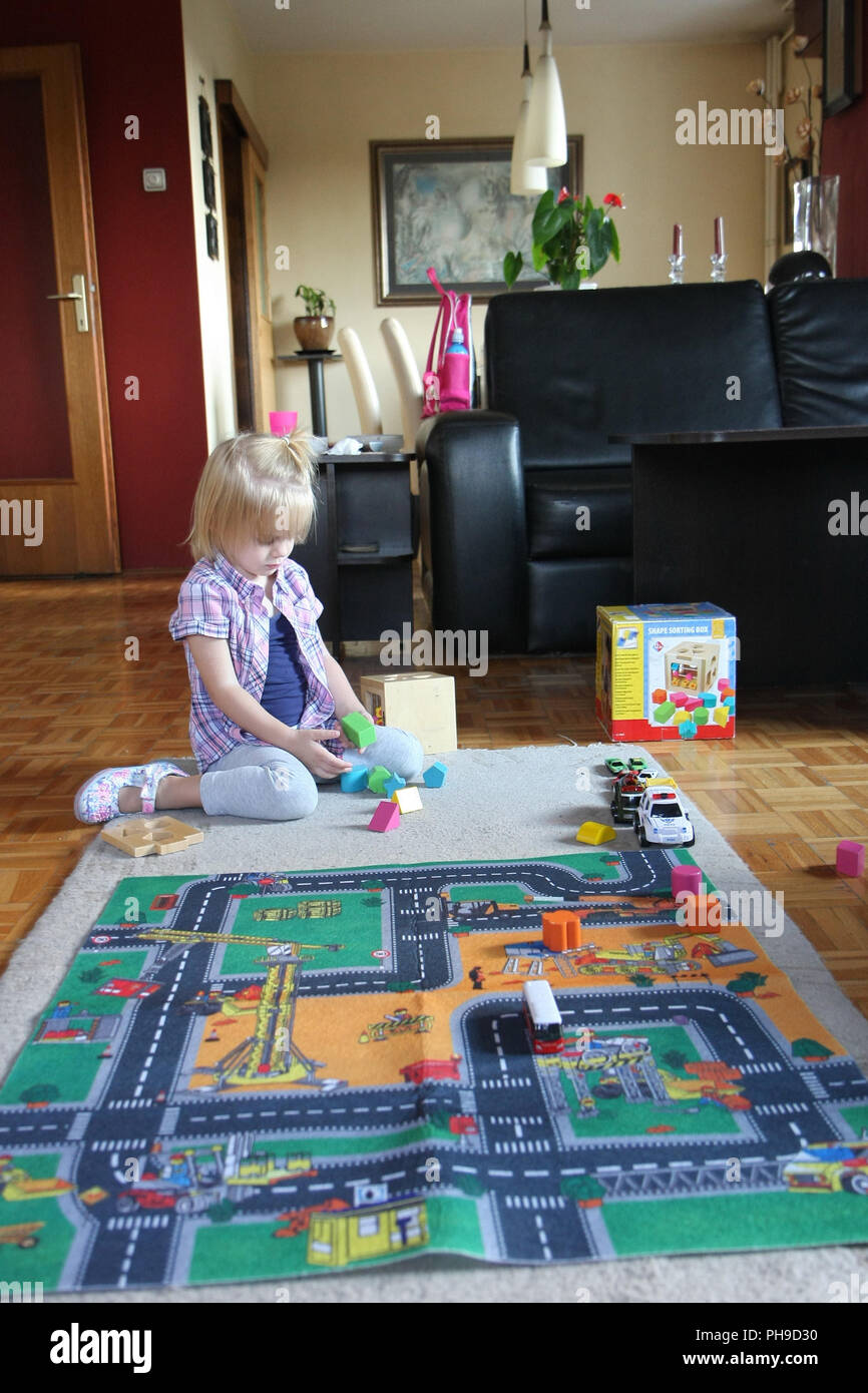 Young girl playing on the floor - Stock Image
