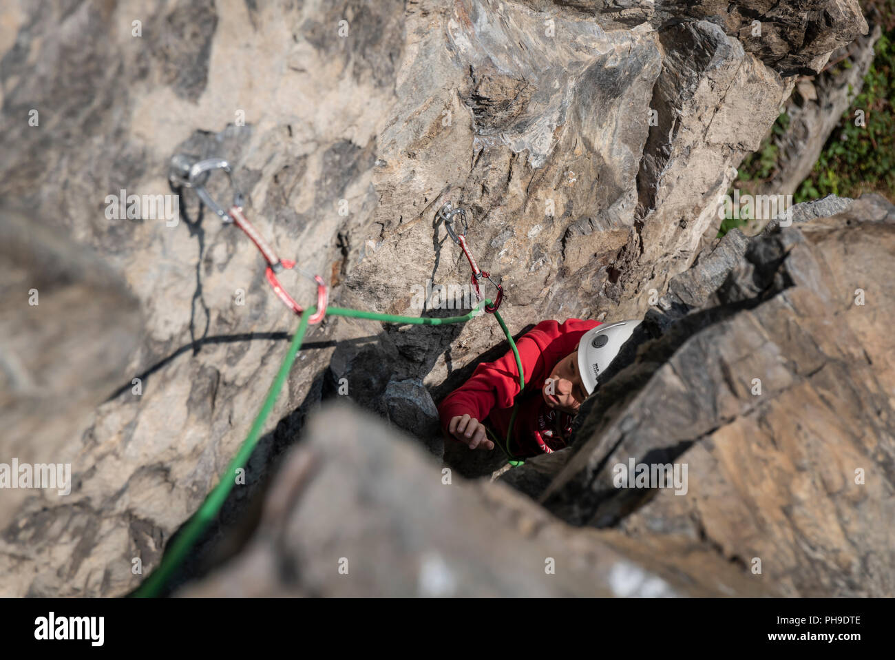 A young boy on a multi pitch rock climb in the Rhone valley, Switzerland Stock Photo