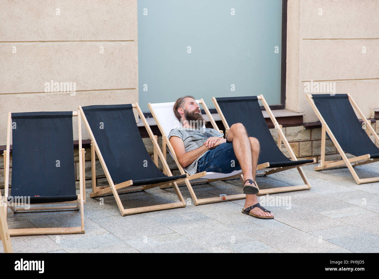 Man with a beard resting and relaxing on a deckchair in Krosno Poland - Stock Image