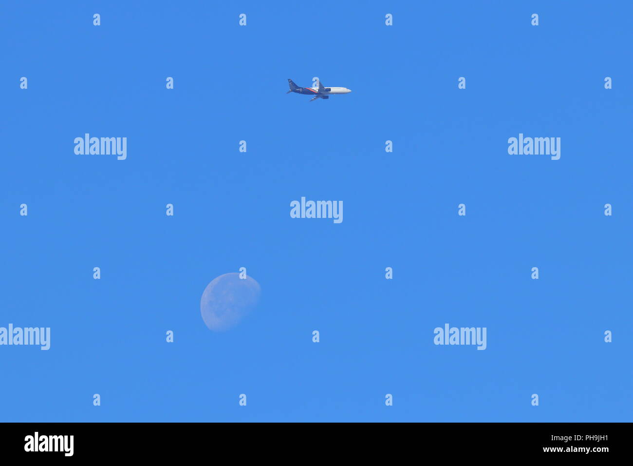 A passenger plane on final approach to Leeds Bradford Airport with the Moon in the background. - Stock Image