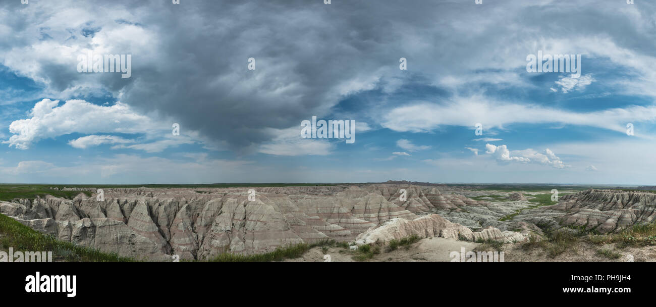 Panorama of Clouds Over Badlands Rock Formation - Stock Image
