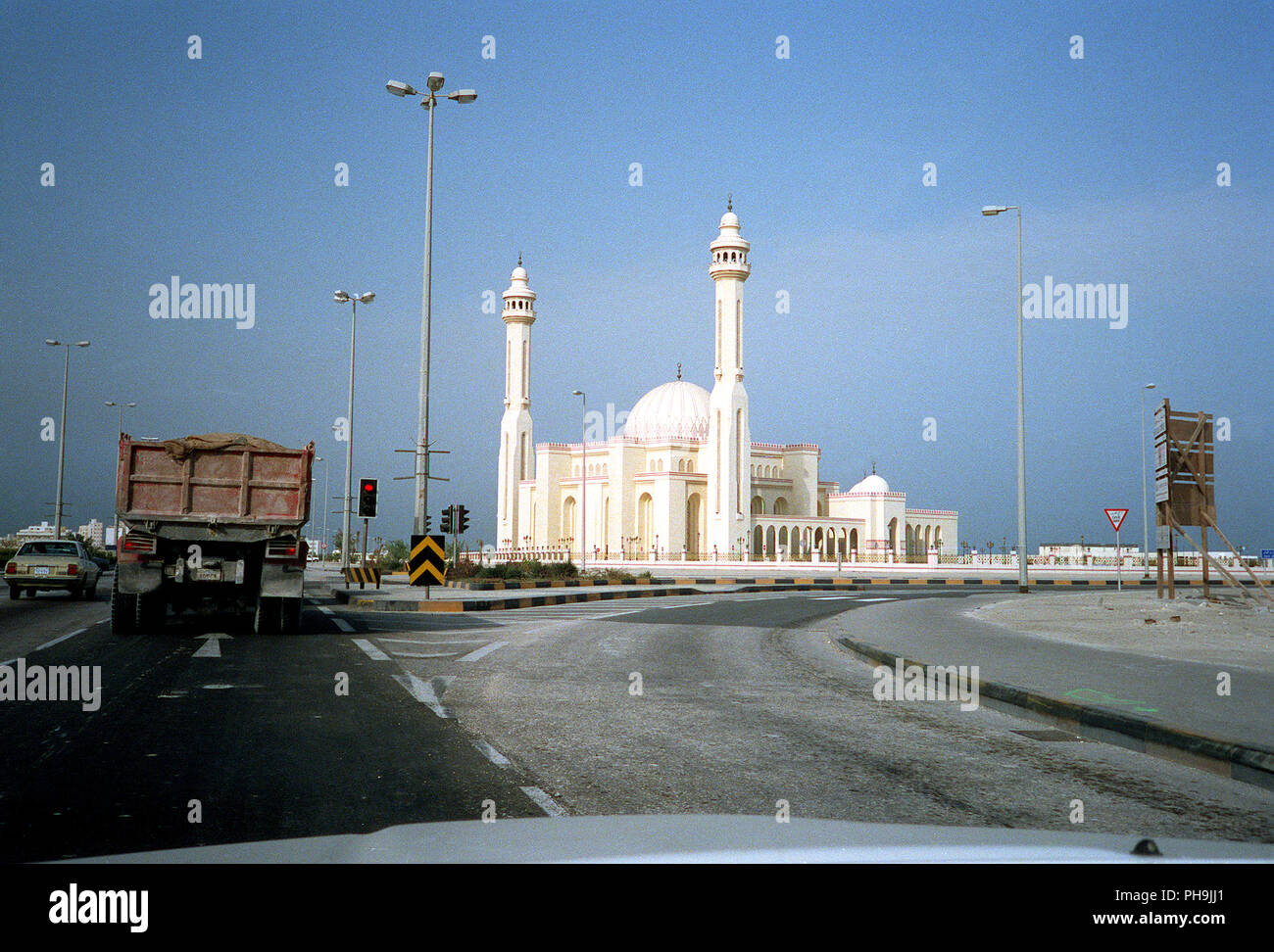 Civilian vehicles wait at a traffic light near a mosque during Operation Desert Storm. - Stock Image