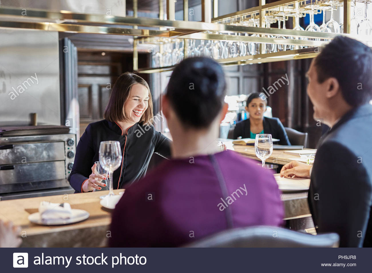 Businesspeople at bar of restaurant - Stock Image
