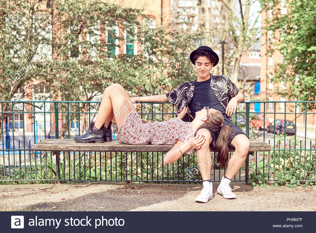 Teenage girl lying in boyfriend's lap at park - Stock Image