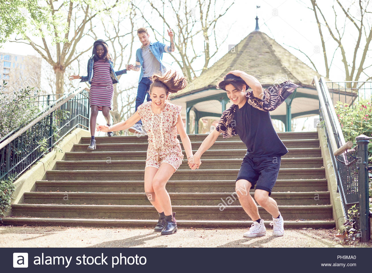 Teenage friends jumping down steps at park - Stock Image