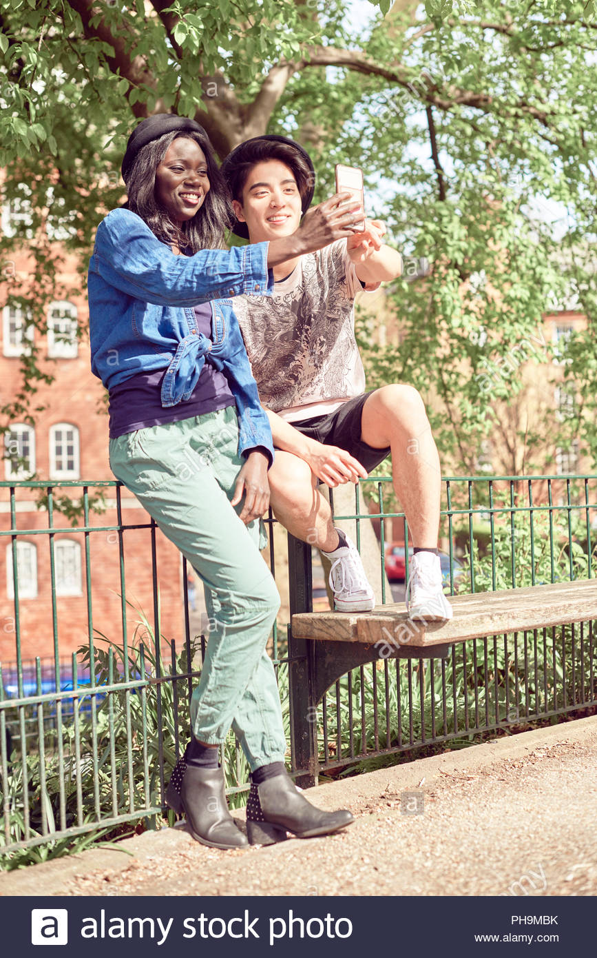 Teenage couple taking selfie in park together - Stock Image