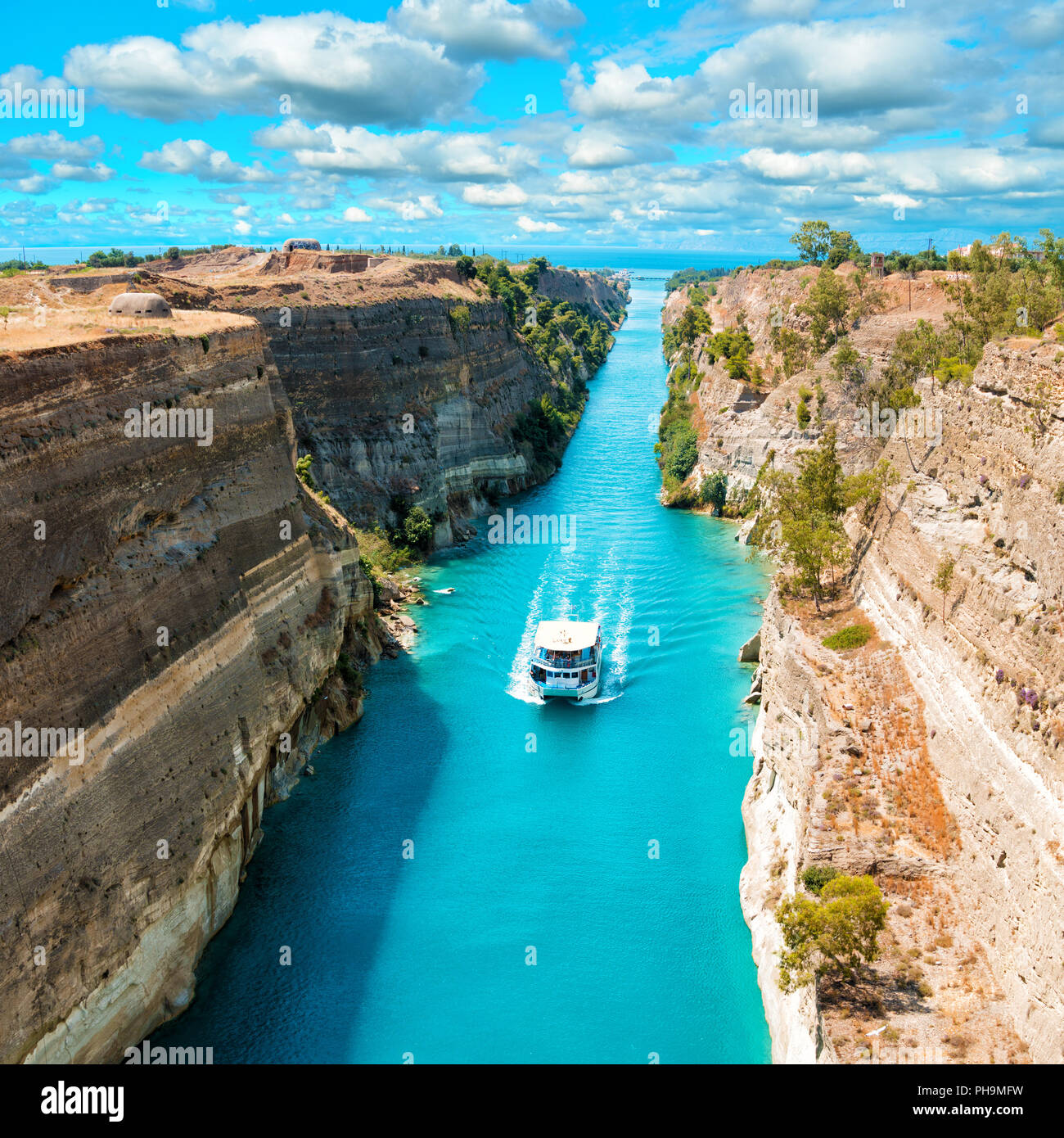 Beautiful scenery of the Corinth Canal in a bright sunny day against a blue sky with white clouds. White ship floating among the rocks Stock Photo