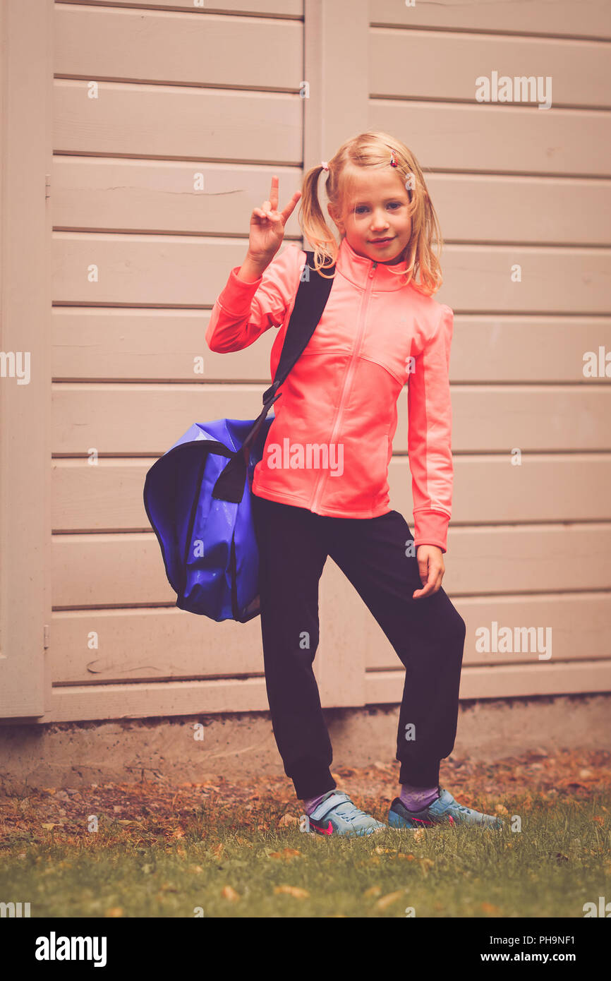 Young girl aged 5-7 showing victory sign Stock Photo