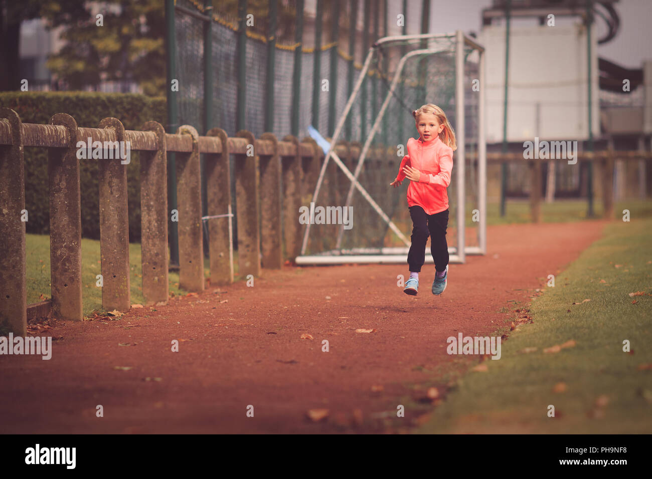 Young girl aged 5-7 running on athletic race track Stock Photo