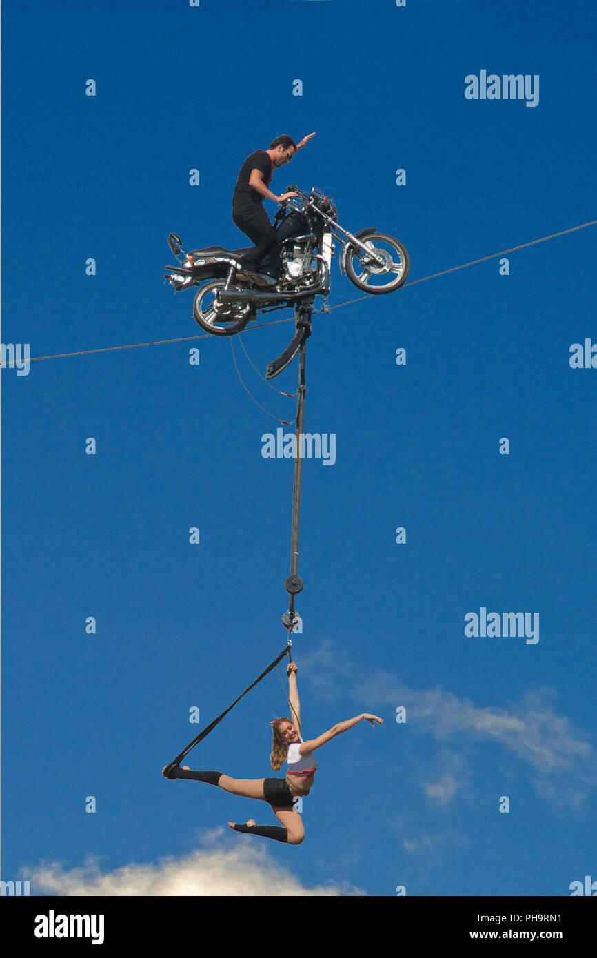 Motorbike stunt rider on wire with girl acrobat Albert Park Melbourne Victoria Australia - Stock Image