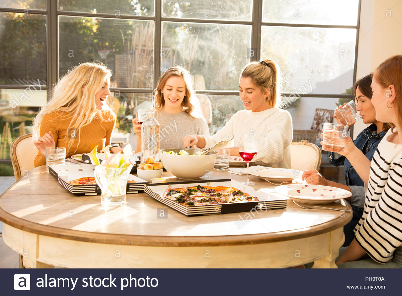 Young women eating pizza together - Stock Image