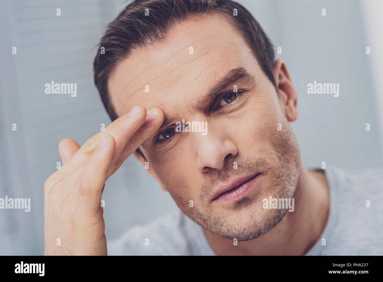 Mature man touching his eyebrow while having migraine - Stock Image