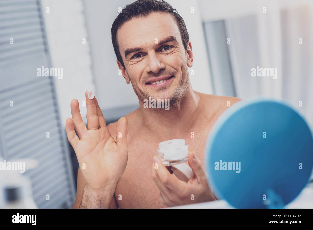 Smiling muscleman using face cream - Stock Image