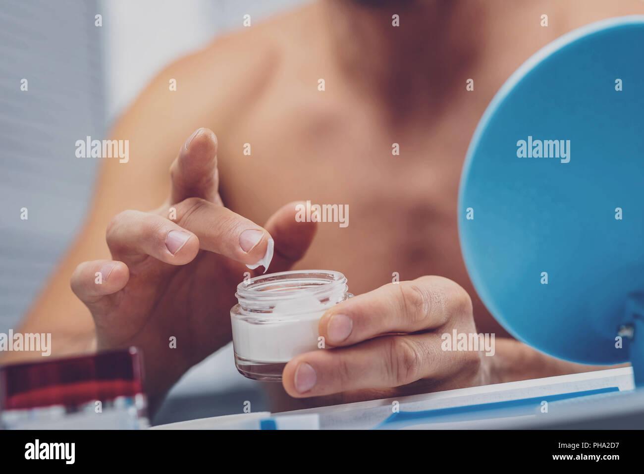 Man holding moisturizing face cream - Stock Image