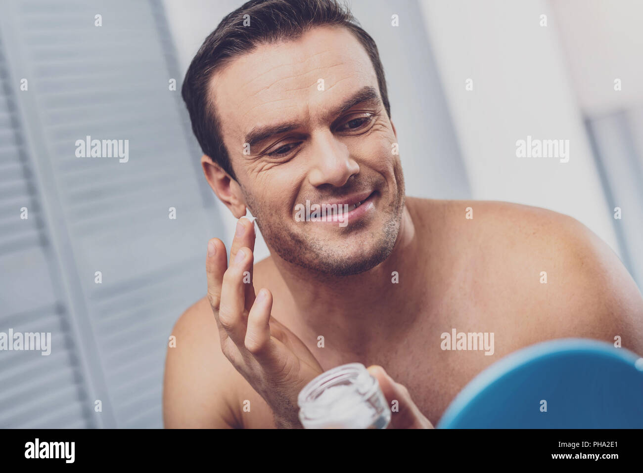 Man with bristle face using face cream - Stock Image