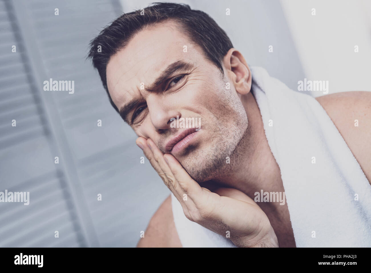 Diseased man suffering from tooth pain - Stock Image