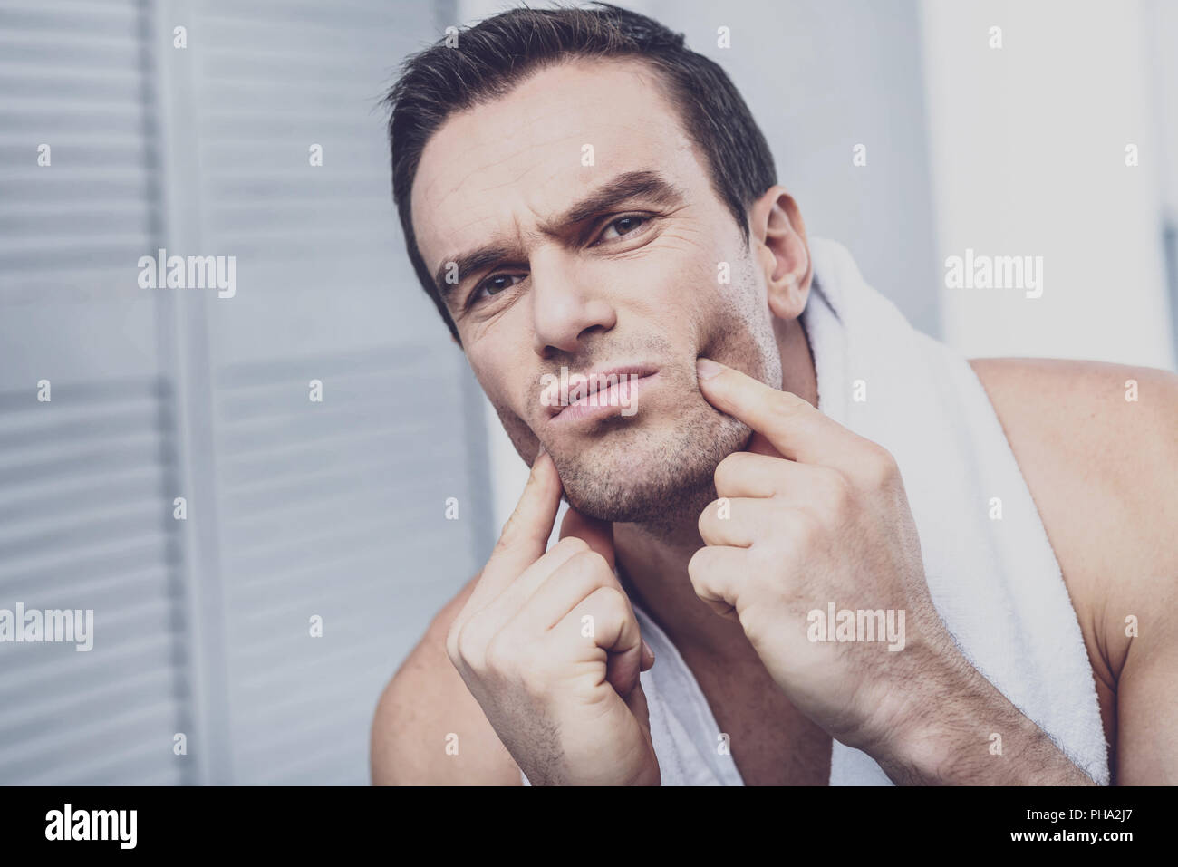 Serious man pressing fingers on his cheeks - Stock Image