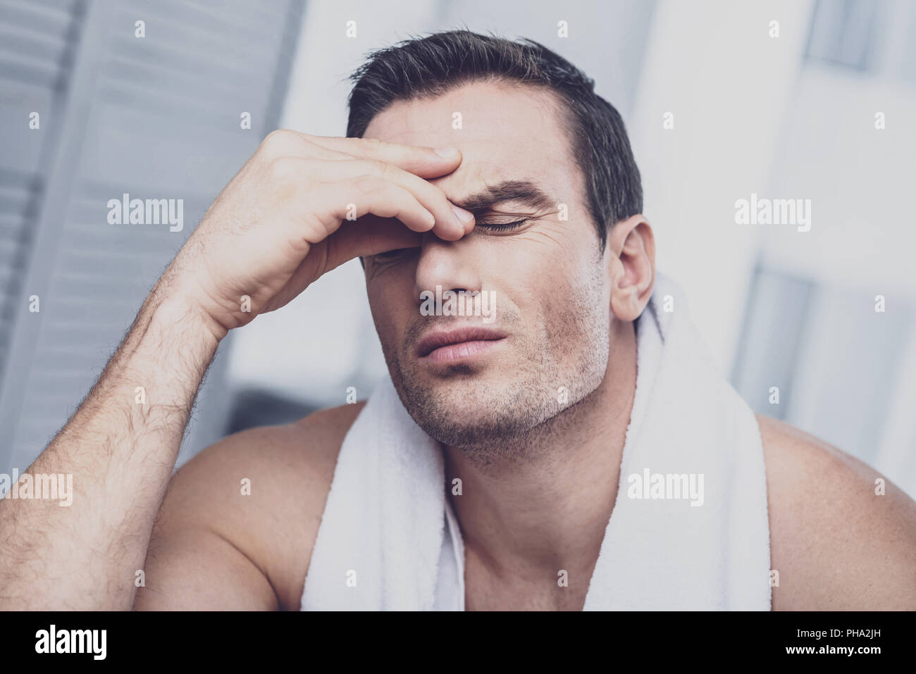 Tired man compressing nose with the finge - Stock Image