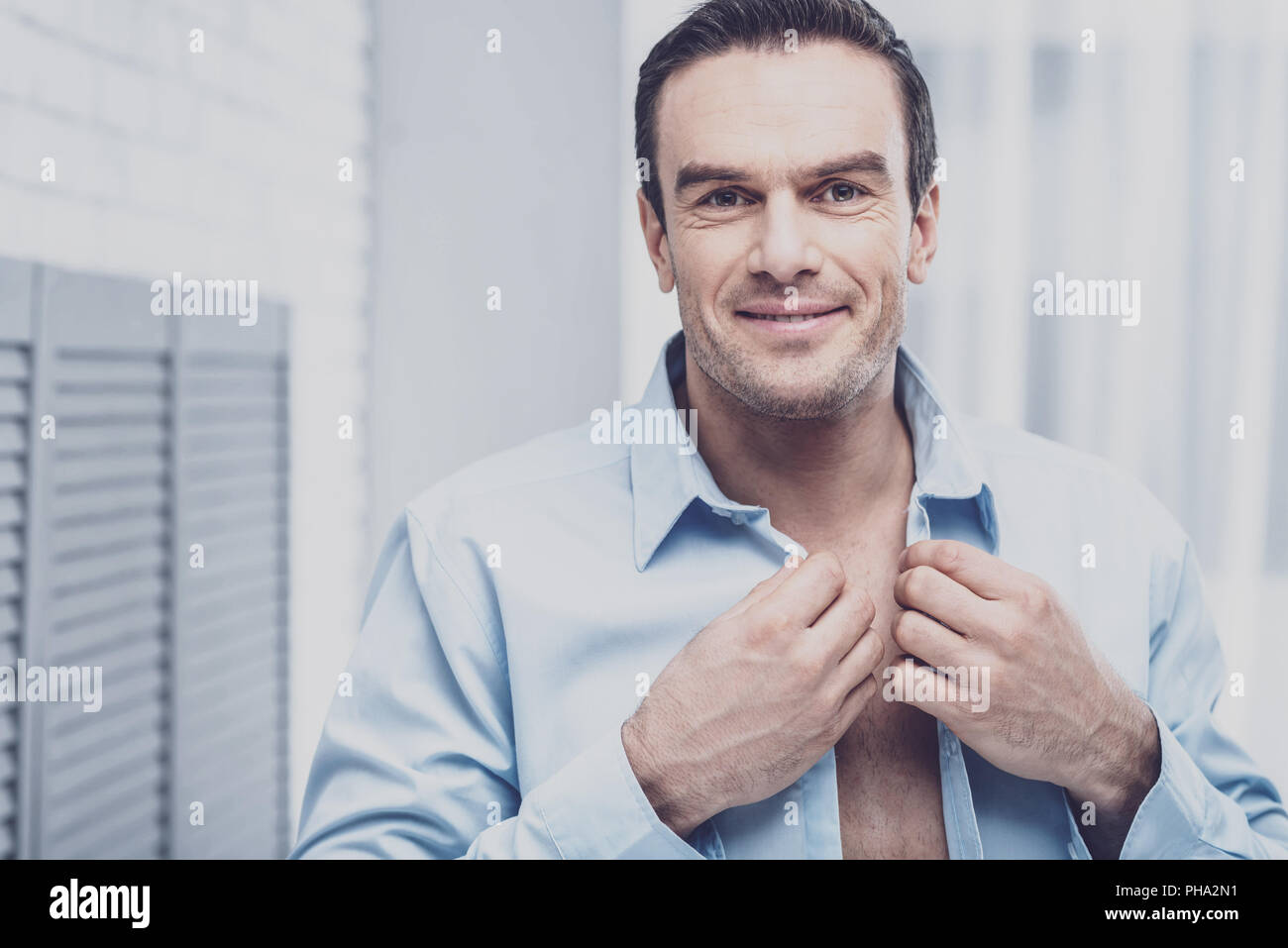 Personable businessman buttoning the shirt - Stock Image