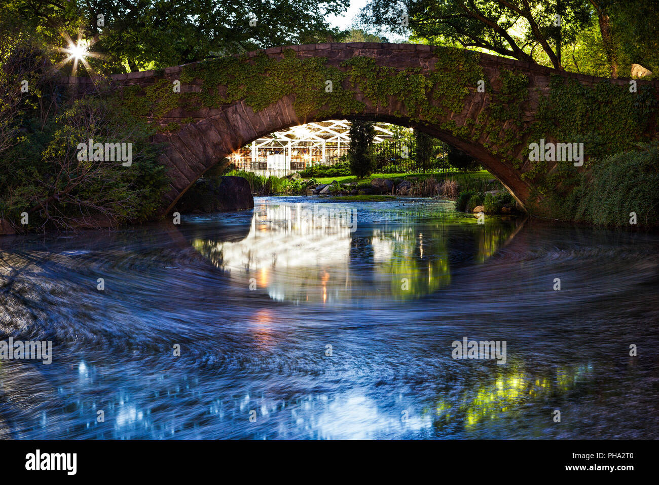 The pond beneath Gapstow Bridge in New York's Central Park reflects the evening light. - Stock Image