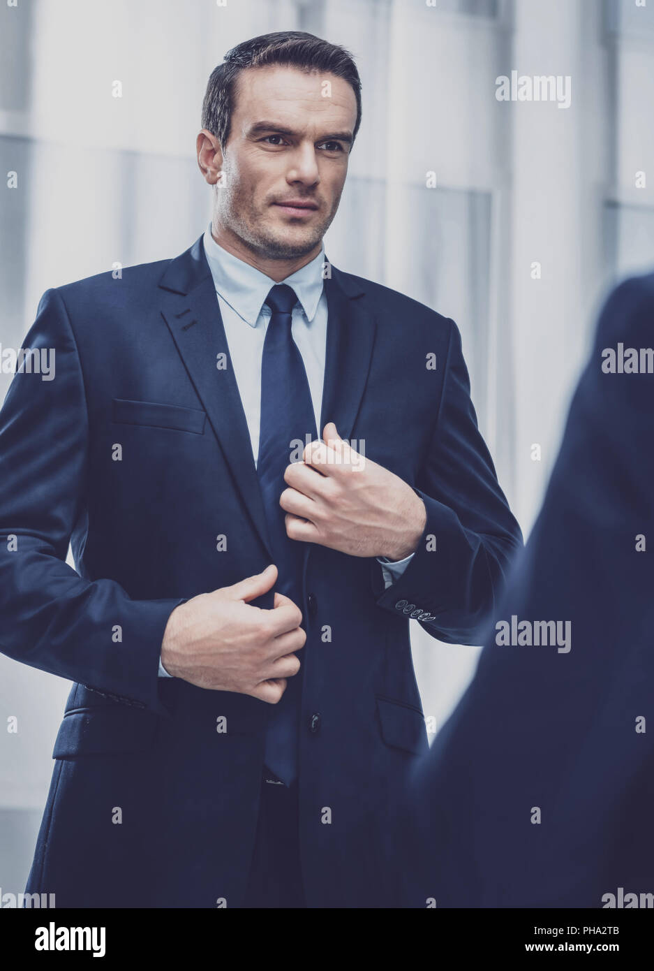 Handsome man trying on jacket - Stock Image